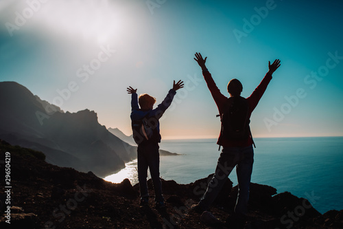 silhouette of happy father and son travel at sunset mountains near sea