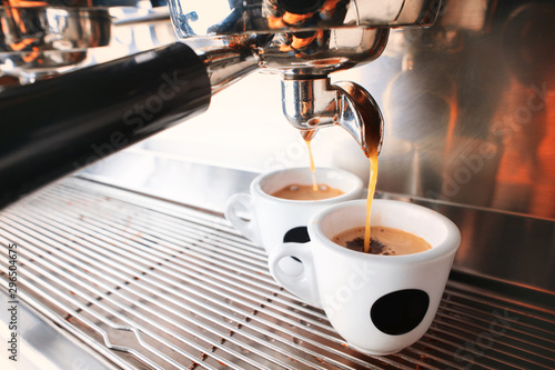 Photo sur Aluminium Cafe Start your day with cup of aromatic drink. Stylish black espresso making machine brewing two cups of coffee, shooted in cafe.