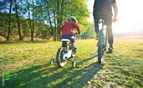 Fotografia  Father and son together are riding bicycles through the pathway in the field