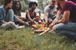 canvas print picture - Roasting over fire flames. Group of people have picnic on the beach. Friends have fun at weekend time