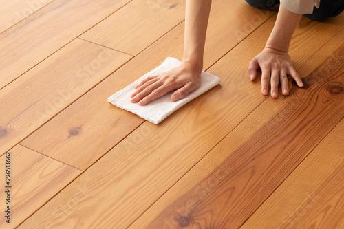 Obraz 木目の床を雑巾で拭く若い女性の手元 - fototapety do salonu