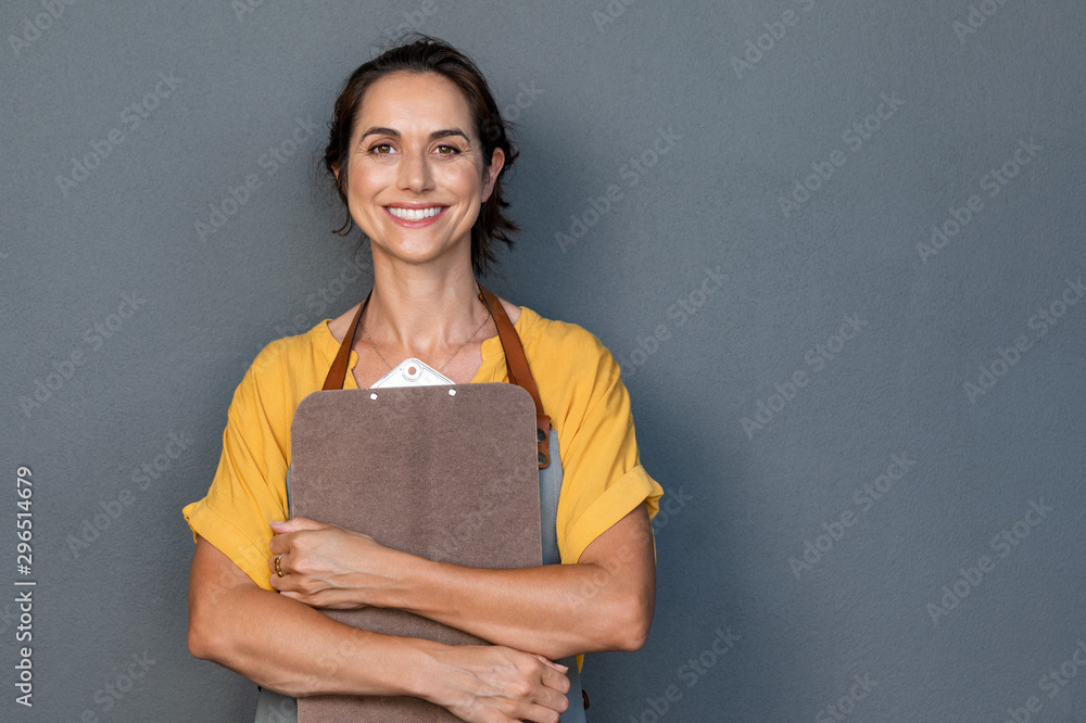 Fototapety, obrazy: Woman entrepreneur in apron looking at camera