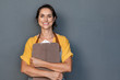 Woman entrepreneur in apron looking at camera