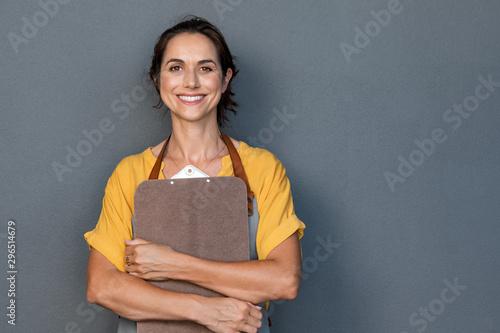 Stampa su Tela  Woman entrepreneur in apron looking at camera