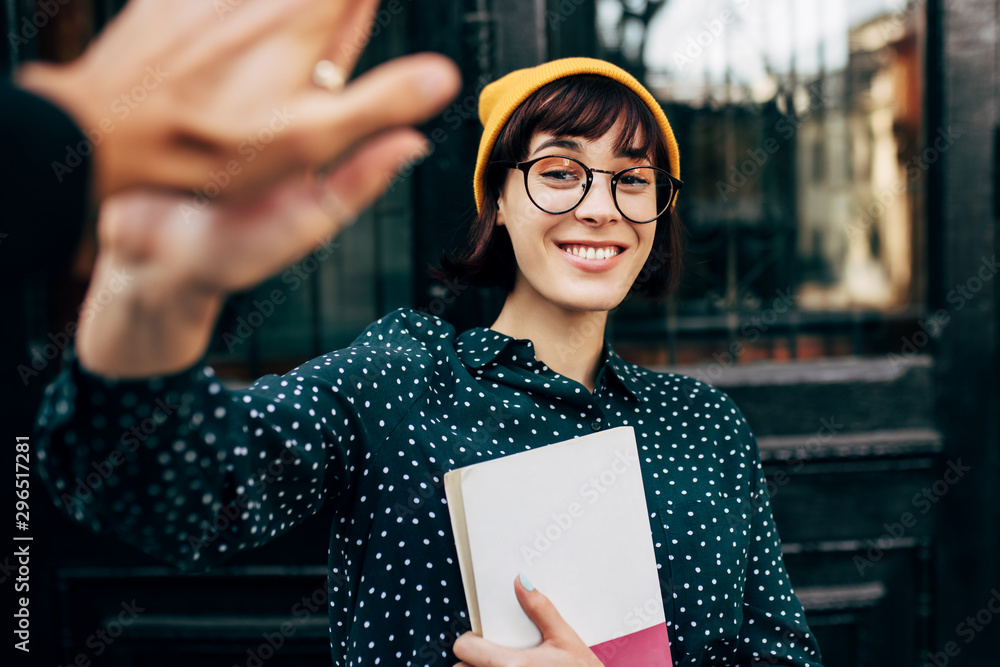 Fototapeta Stylish young female student giving high five outdoor, celebrating successful examination at college. Happy young woman giving five to friend during friendly collaboration on studying project