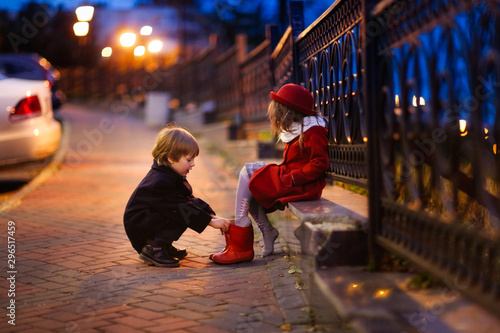 boy helps a girl to shoe boots, evening street