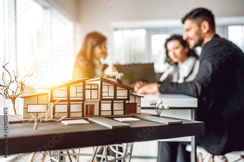 Cuadros en Lienzo Close up image of house model with group business people on blurred background in building design studio
