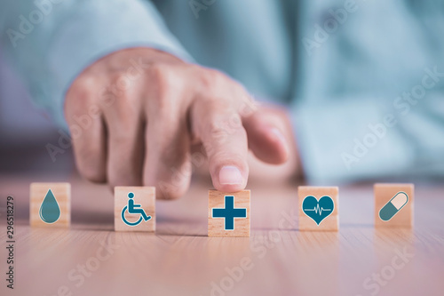 Papiers peints Pharmacie Businessman chooses a emoticon icons healthcare medical symbol on wooden block , Healthcare and medical Insurance concept