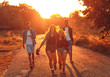 canvas print picture - Group of four friends having fun hiking through countryside together on road during sunset.
