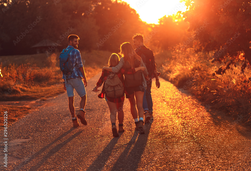 Fototapety, obrazy: Group of four friends having fun hiking through countryside together on road during sunset.