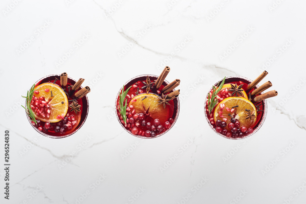 Fototapeta top view of christmas cocktails with orange, pomegranate and cinnamon