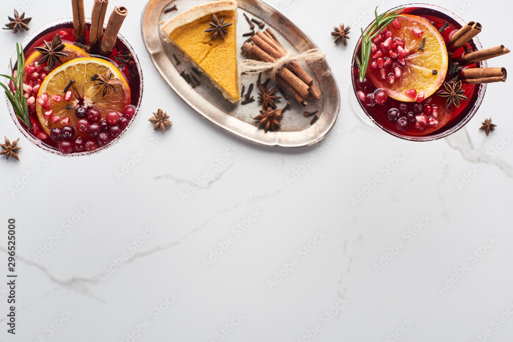 Fototapeta top view of christmas cocktails with orange, pomegranate, cinnamon and pie on tray
