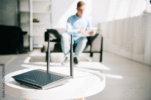 selective focus of black plugged router on white table and businessman sitting o Canvas Print