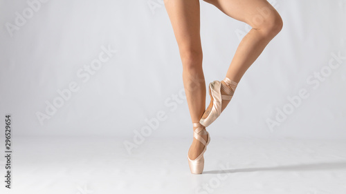 Fototapeta  Close-up of dancing legs of ballerina wearing white pointe on a white background