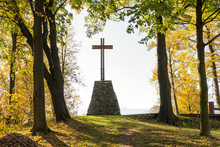 Wooden Christian Religious Cross On The Background Of Green Trees