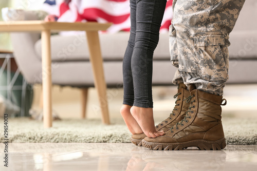 Pinturas sobre lienzo  Girl standing on feet of her military father at home