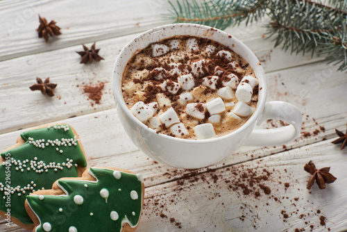 cacao with marshmallow in mug on white wooden table with fir branch and Christmas cookies