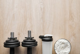 top view of heavy dumbbells near sports bottle and jar on wooden surface