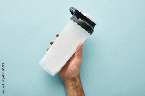 fototapeta na szkło cropped view of man holding sports bottle with protein shake on blue