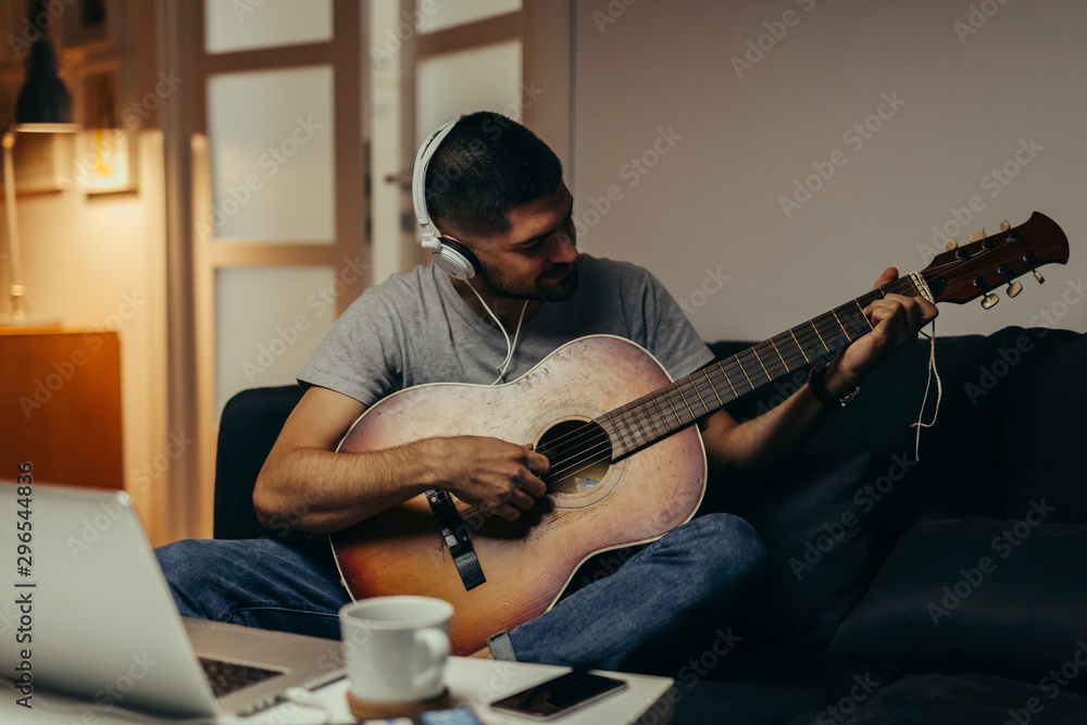 Fototapety, obrazy: man playing guitar at his home