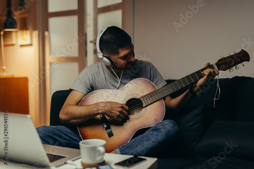 man playing guitar at his home - 296544836