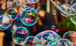 canvas print picture - Metallic glowing colorful soap bubble in the air in front of a blurry abstract background