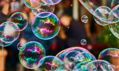 Fototapeta Metallic glowing colorful soap bubble in the air in front of a blurry abstract background obraz
