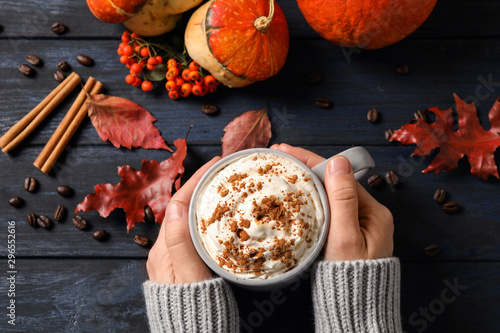 Fotografie, Obraz  Woman with cup of tasty pumpkin spice latte at wooden table, top view