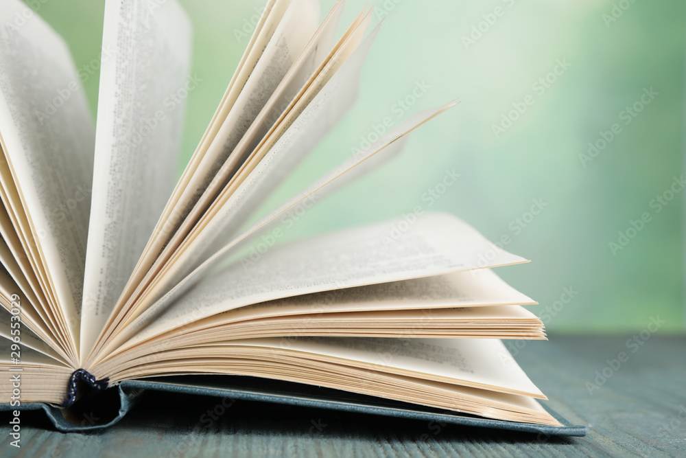 Fototapety, obrazy: Open book on blue wooden table against blurred green background, closeup