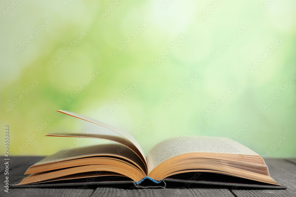 Fototapety, obrazy: Open book on blue wooden table against blurred green background. Space for text