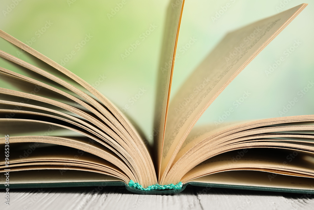 Fototapety, obrazy: Open book on white wooden table against blurred green background, closeup