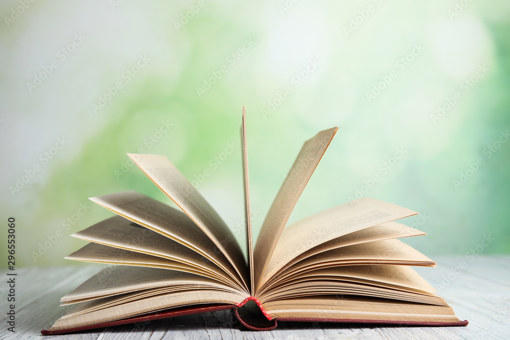 Fototapety, obrazy: Open book on white wooden table against blurred green background