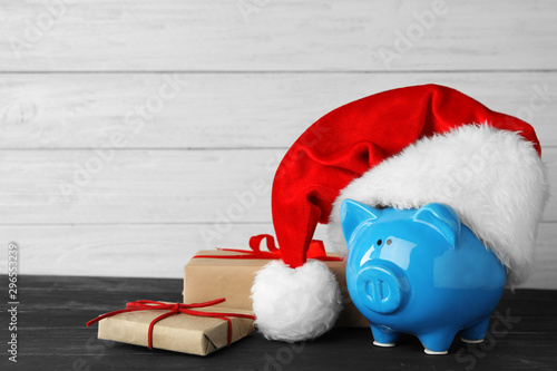 Piggy bank with Santa hat and gift boxes on black wooden table. Space for text