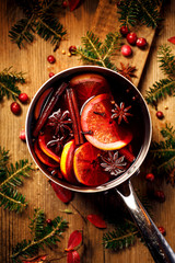 Christmas mulled red wine with the addition of spices and citrus fruits in a pot on a rustic wooden table, top view. Pot of mulled wine, traditional christmas drink.