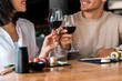 canvas print picture - cropped view of happy man and cheerful woman clinking glasses with red wine near sushi