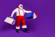 canvas print picture - Full length body size view of his he nice cheery glad cheerful positive bearded thick fat Santa carrying bags new clothes clothing going isolated on bright vivid shine vibrant violet lilac background