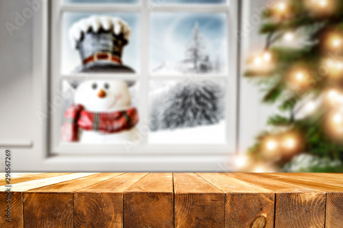 Desk of free space for your decoration and winter window background with snowman  - 296567269