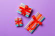 canvas print picture - wrapped Christmas or other holiday handmade present in paper with red ribbon on purple background. Present box, decoration of gift on colored table, top view
