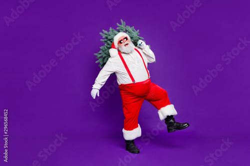 Let it snow. Full length photo of funny fat santa father holding x-mas tree on shoulder wanna make perfect eve wear sun specs costume isolated purple background - 296568452