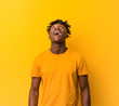 canvas print picture - Young black man wearing rastas over yellow background relaxed and happy laughing, neck stretched showing teeth.