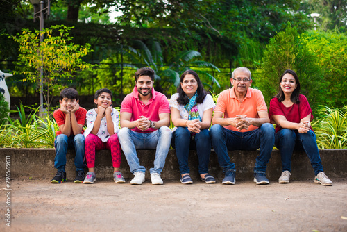 Spoed Fotobehang Japan Indian Family enjoying Picnic - Multi generation of asian family sitting over or near small wall in park, outdoor. selective focus