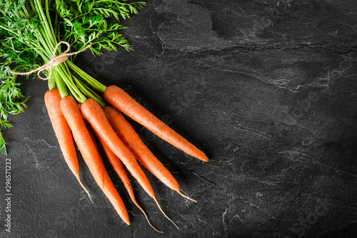 Fototapeta Fresh carrot on dark stone table or black background top view. obraz