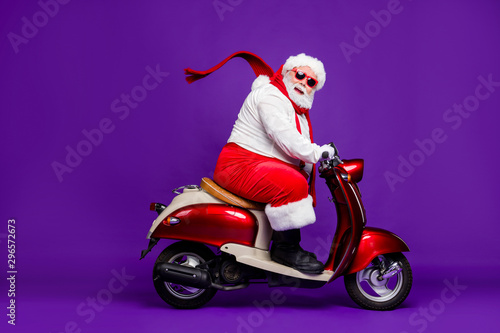 Photo of fat santa claus role man rushing newyear x-mas theme party by bike cool modern style wear sun spectacles trousers hat suspenders isolated purple background