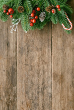 Wood Table Plank In Vertical With Pine Leaves And Pine Cones, Holly Balls And Candy Cane In Christmas Theme Concept. Wooden Background In Top View Flat Lay With Copy Space For Christmas Wallpaper.