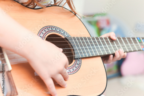 Obraz na plátne  Girl learns to play guitar during a music lesson on the instrument