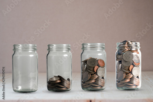 Fototapeta Money coins growing in jar. Profit on deposit in bank and dividend for stock investment concept. obraz