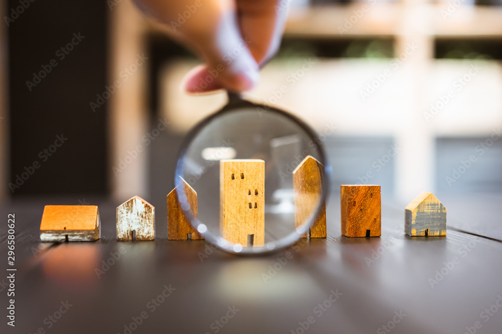 Fototapeta Hand holding magnifying glass and looking at house model, house selection, real estate concept.