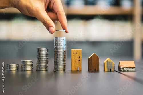 Hand choosing row of coin money on wood table and mini wood house, selective focus, Planning to buy property Wallpaper Mural
