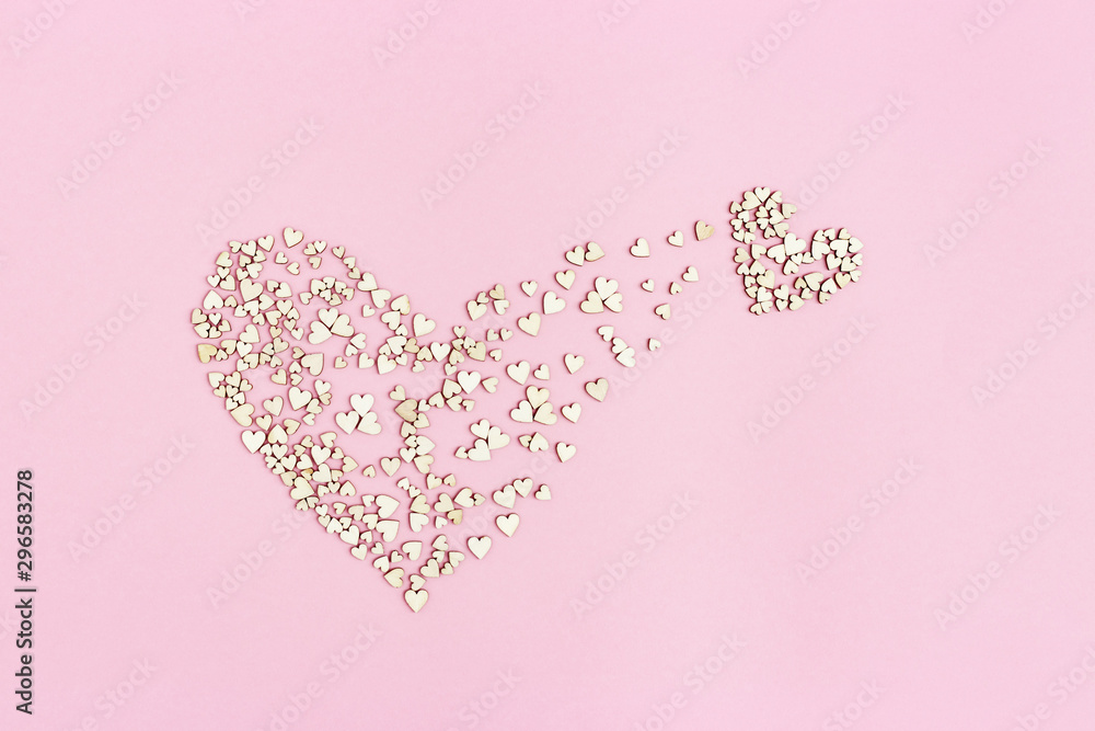 Fototapety, obrazy: Small heart emerges from large one. Birth of new love. Concept of love. Many small wooden hearts on pink background. Flat lay.