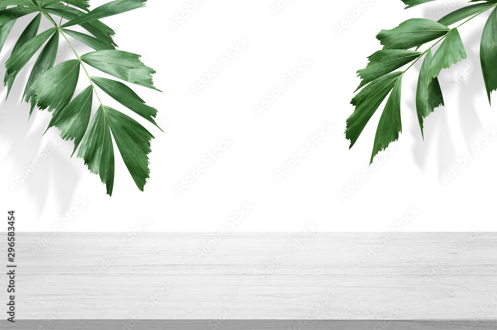 Fototapeta white wooden table top with green palm leave for product advertisement display